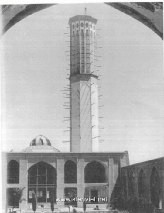 Hình 1: HỆ THỐNG LÀM MÁT TỰ ĐỘNG làm mát toà nhà ở thành phố Yazd, Iran: tháp đo gió, mái vòm và lỗ thông hơi. Tháp đo gió có tác dụng làm mát không khí bên ngoài và lưu thông gió trong toà nhà. (Hai đầu của xà gỗ dùng để gia cố công trình nhô ra khỏi toà tháp, hai đầu được đặt ở đó tạo giá đỡ cho giàn giáo để bảo quản toà tháp.) Mái vòm ở bên trái toà tháp có tác dụng giữ cho căn phòng dưới mái luôn mát mẻ. Kết cấu hẹp trên nóc mái vòm bao phủ lỗ thông hơi có vai trò giữ căn phòng phía dưới luôn luôn mát mẻ và duy trì sự lưu thông không khí trong ngôi nhà. Ba hệ thống giữ cho toà nhà dễ chịu trong suốt những tháng mùa hè.