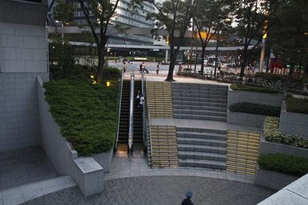 Ngay bên quảng trường lớn có bậc thang bộ gắn đèn sáng và thang máy đi xuống…