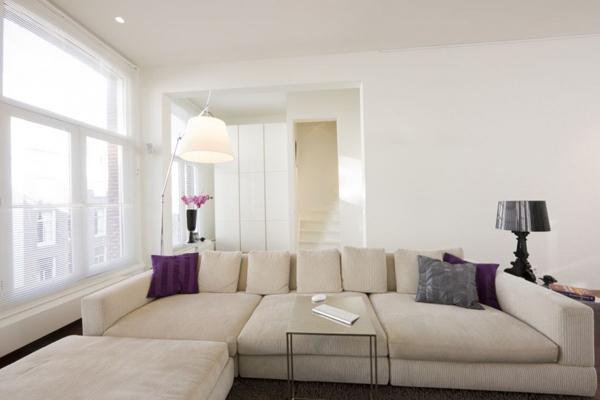 Ghế Sofa phòng khách thiết kế khá đơn giản, tông màu hài hòa với sắc trắng chủ đạo, điểm xuyết là các sắc tím (mang giá trị trung tính)
