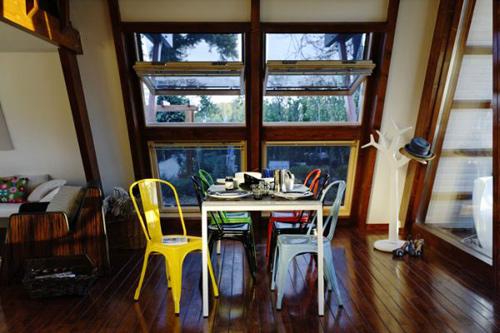 Bộ bàn ăn vui mắt với những chiếc ghế nhựa nhiều màu sắc.