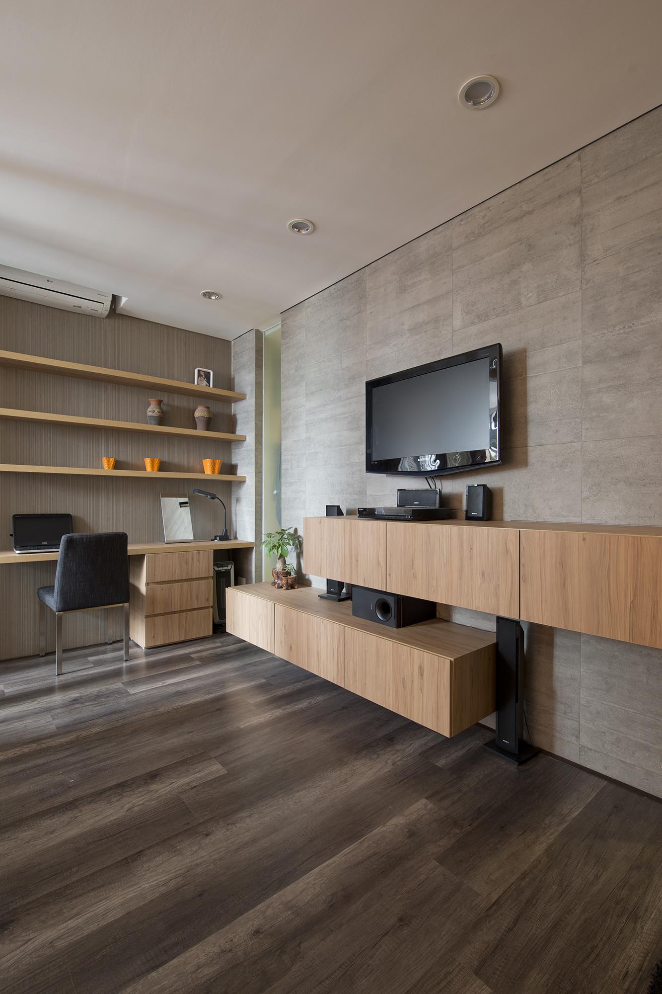 Hệ thống kệ TV treo tường liên hoàn với góc làm việc đơn giản. Chất liệu sàn gỗ, đồ nội thất, tường gạch bê tông trần được kết hợp với nhau tạo thành một tổng thể thống nhất