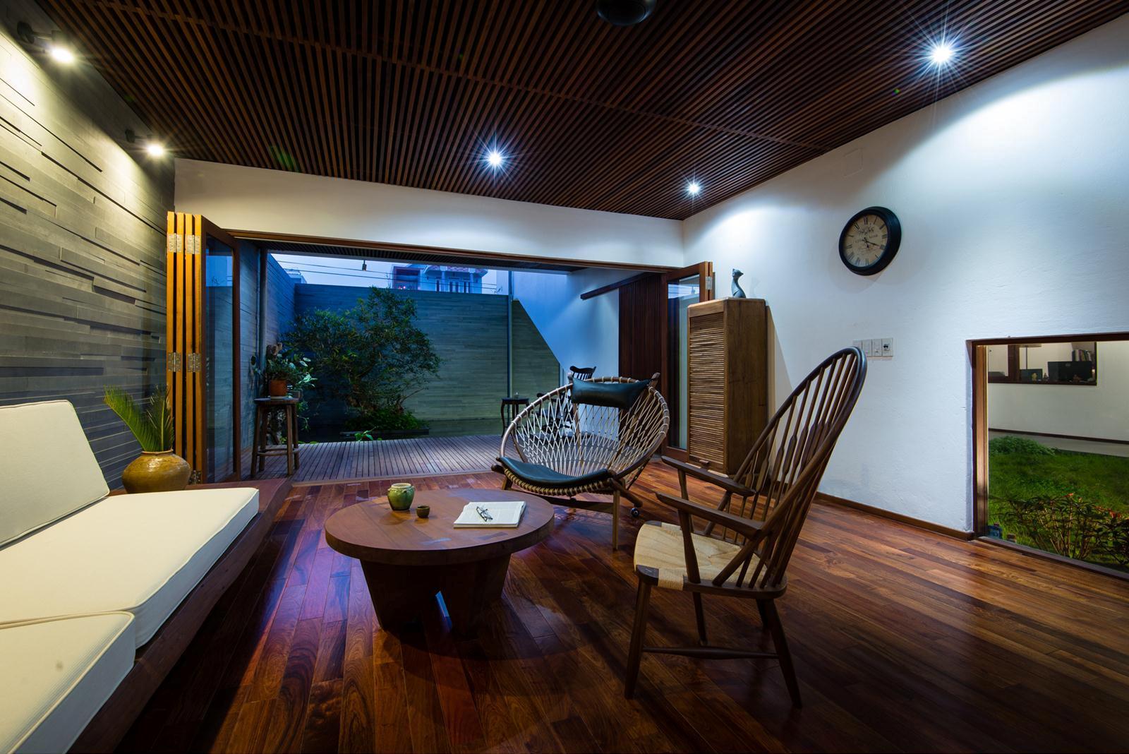 Phòng khách buổi tối nhìn ra không gian vườn trước nhà