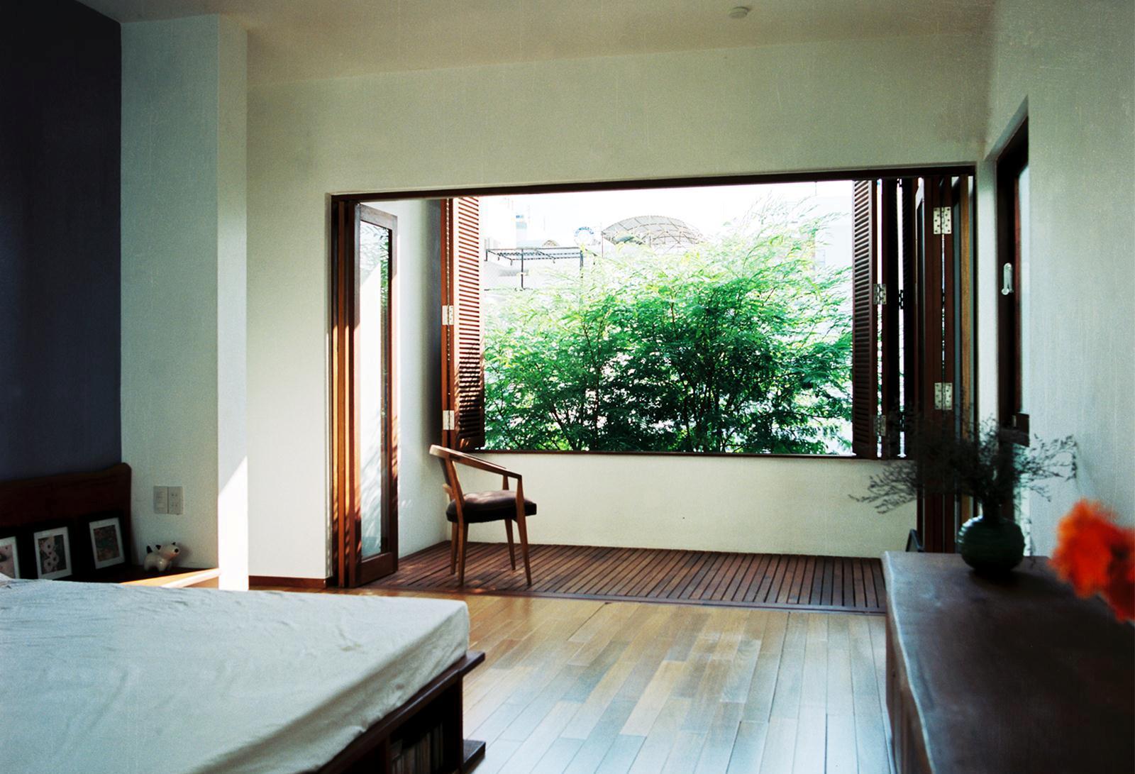 Phòng ngủ chính với không gian đệm nhìn ra khoảng xanh