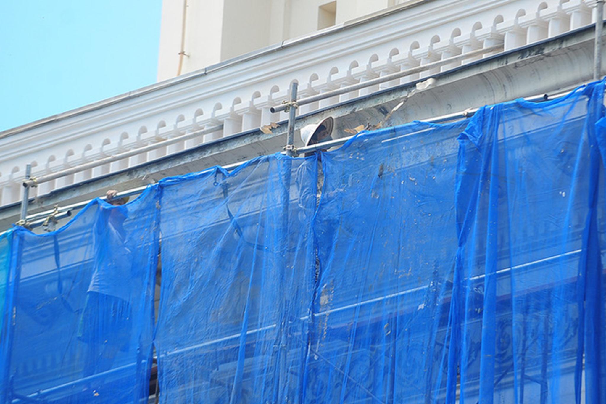 Phía sau của Nhà hát được quây lưới kín, các công nhân đang bóc những lớp sơn cũ bong tróc từ trước.