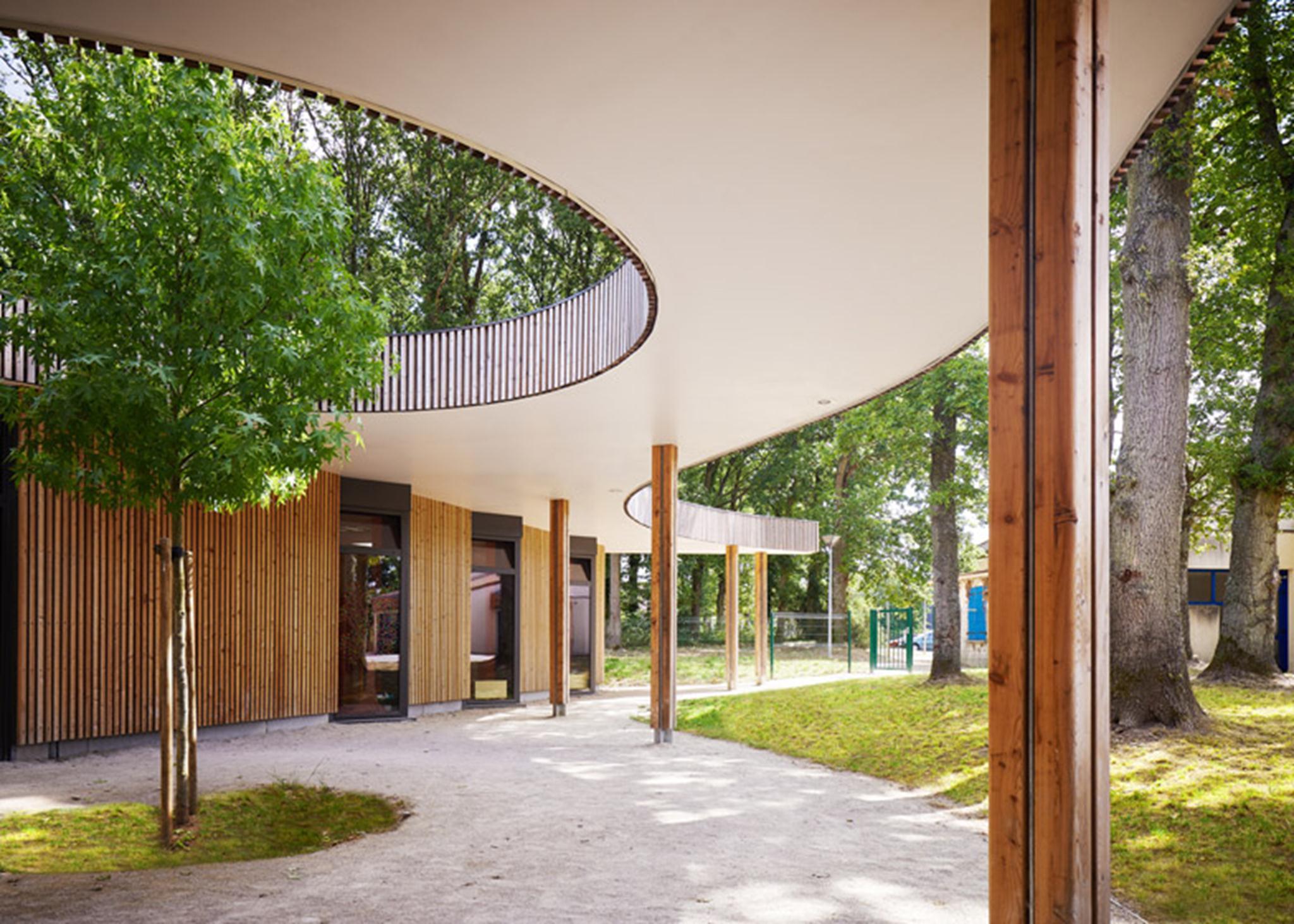 Một bức tường kính lõm nới rộng vào khu vực tiếp tân trung tâm và được bao quanh bởi một khu vườn nhỏ, góp phần vào cảm giác tươi sáng và cởi mở cho không gian.