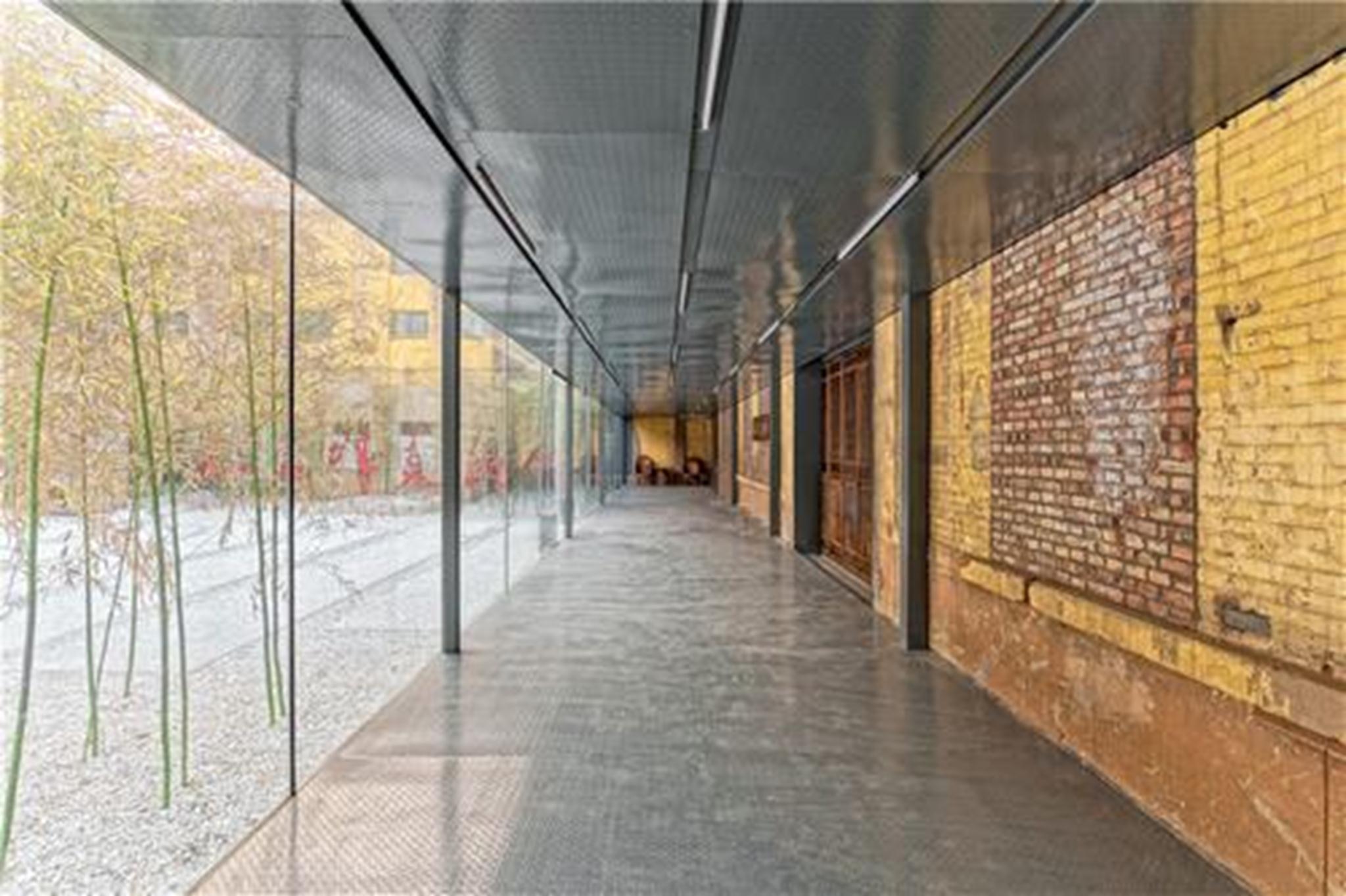 Một hành lang mờ kết nối nội thất và ngoại thất và làm nổi bật sự tương phản giữa những đặc điểm cũ và mới