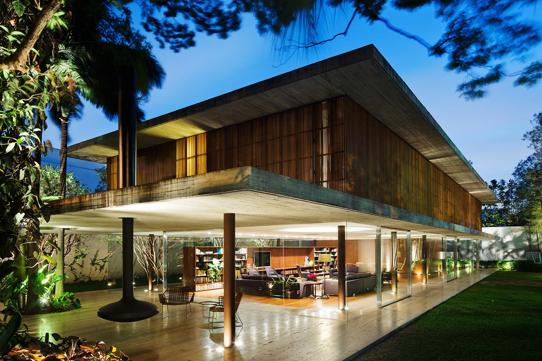 Phòng khách được tiếp nối mở rộng bởi một hiên ngoài với lò sưởi treo bằng thép